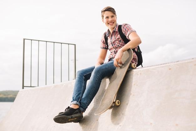 Adolescente com skateboard sentado na rampa