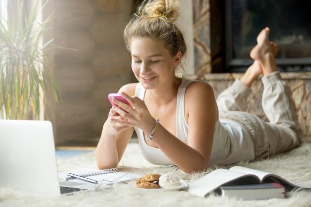 Adolescente com smartphone em casa