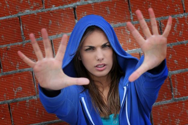 Adolescente, com, suéter azul, mostrando, mão, para, câmera