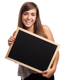 Adolescente com um grande sorriso que levanta com um quadro-negro