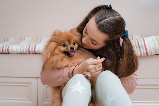 Adolescente com uma raça de cachorro spitz se alegra com um animal de estimação em casa no chão.
