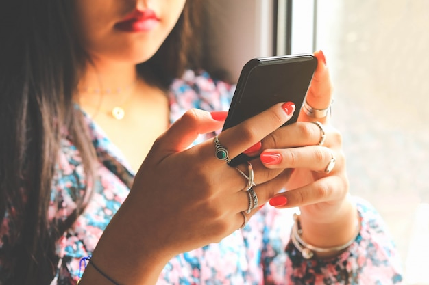 Adolescente com unhas de manicure vermelho usando smartphone moderno perto da janela