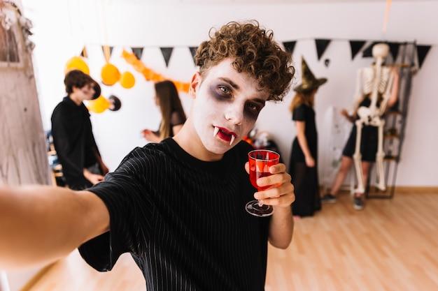 Adolescente com vampiro sombrio na festa de halloween