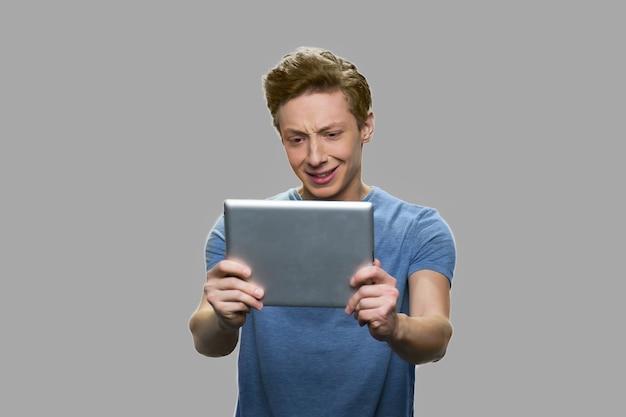Adolescente com videochamada. adolescente falando com alguém via internet usando o tablet pc contra um fundo cinza.