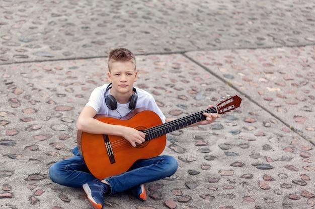 Adolescente com violão e fones de ouvido, sentado no parque.
