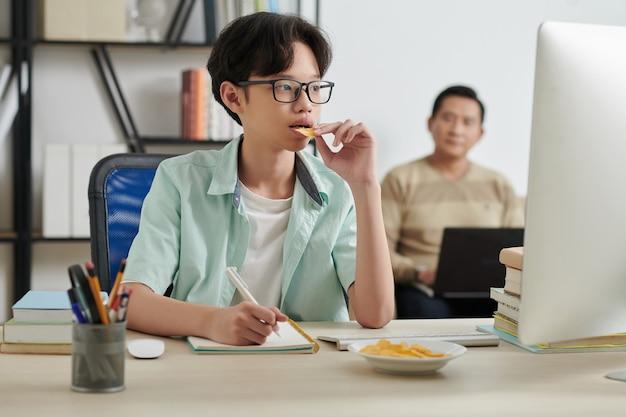 Adolescente comendo batata frita e assistindo à aula online no computador enquanto estuda em casa, seu pai está trabalhando em segundo plano