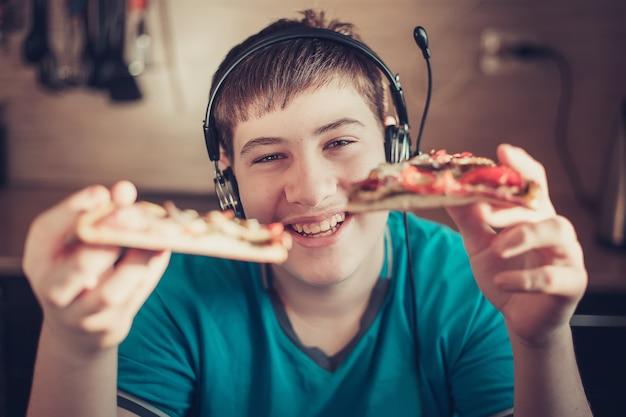Adolescente comendo pizza sentado em um laptop.