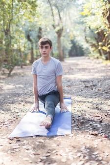 Adolescente concentrado fazendo exercícios de alongamento dura