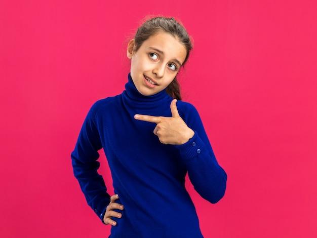 Adolescente confiante segurando a cintura, olhando e apontando para o lado isolado na parede rosa com espaço de cópia