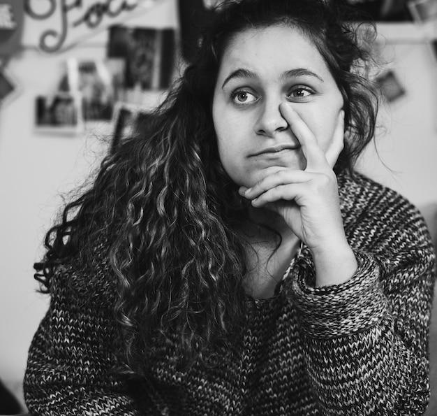 Adolescente confiante, sentado em um quarto com um sinal de paz