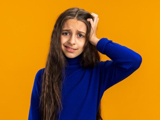 Adolescente confusa mantendo a mão na cabeça isolada na parede laranja