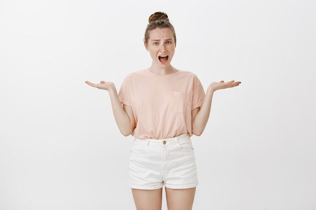 Adolescente confusa posando contra a parede branca