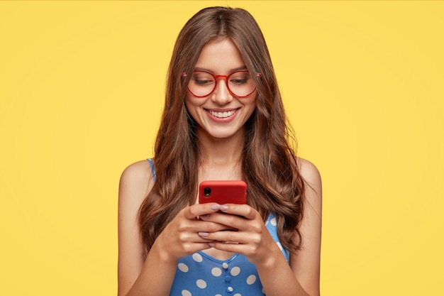 Adolescente contente com cabelo comprido, segura um celular moderno, navega pelas redes sociais, tem expressão alegre