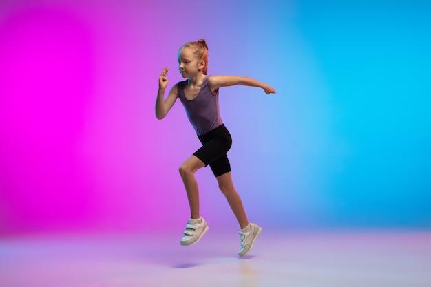 Adolescente correndo correndo contra o fundo do estúdio gradiente de néon rosa azulado em movimento