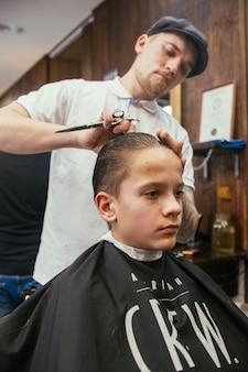 Adolescente corta o cabelo de cabeleireiro na barbearia. penteado retrô elegante na moda. retrato de uma criança com um lindo corte de cabelo.
