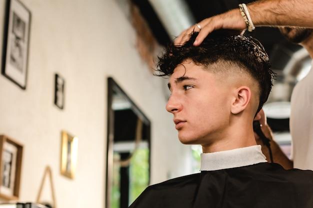 Adolescente, cortando o cabelo moderno em uma barbearia vintage