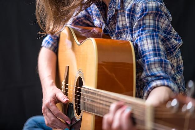Adolescente da menina que joga uma guitarra acústica em um fundo escuro no estúdio. concerto jovens músicos