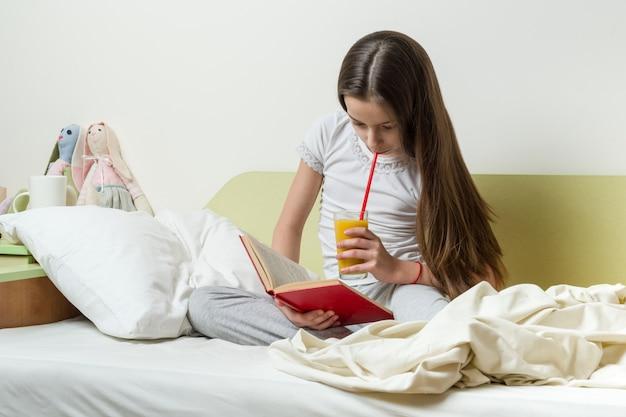 Adolescente de 10 anos em roupas para casa lê um livro na cama no quarto dela