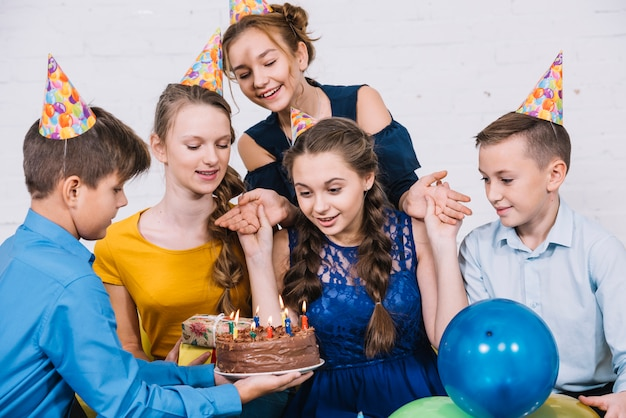 Adolescente de aniversário surpresa olhando bolo trazido por sua amiga