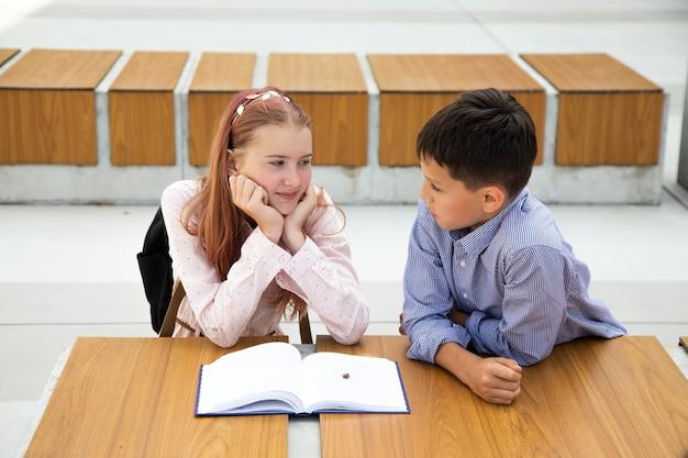 Adolescente de cabelo rosa lê livro, menino de 11 anos, estudante trouxe seu besouro, conceito de relacionamento adolescente