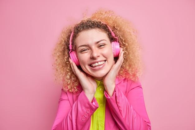 Adolescente de cabelos encaracolados positiva gosta de ouvir música favorita usa fones de ouvido estéreo, estando de bom humor usa roupas brilhantes, isoladas sobre a parede rosa. mulher feliz ouvindo música