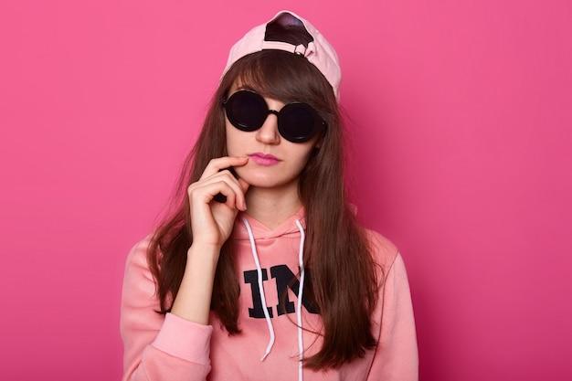 Adolescente de cabelos escuros pensativo, usa roupas elegantes rosa