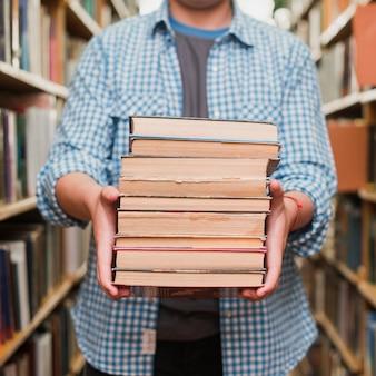 Adolescente de colheita mostrando pilha de livros