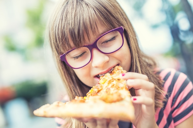 Adolescente de criança menina com pizza. retrato de uma jovem pré-adolescente com um pedaço de pizza. criança com aparelho e óculos. foto tonificada.
