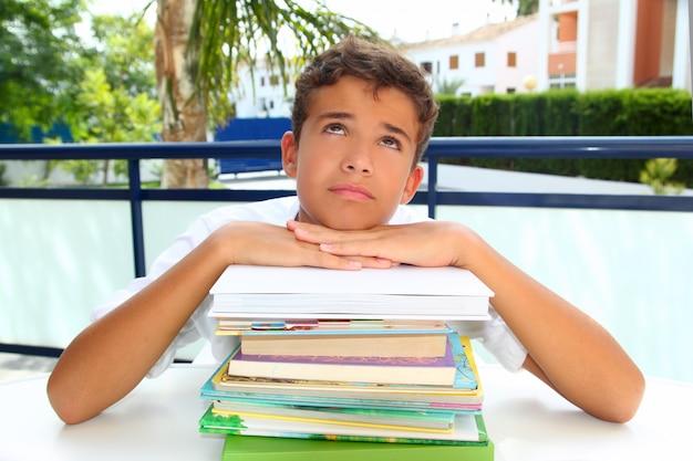 Adolescente de estudante de menino entediado pensando com livros