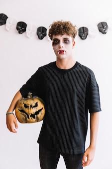Adolescente de halloween com presas de vampiro e abóbora