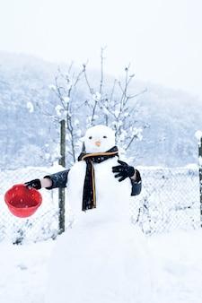 Adolescente de inverno em uma jaqueta e chapéu esculpe um boneco de neve em um fundo de inverno com queda de neve no conceito de dia congelado