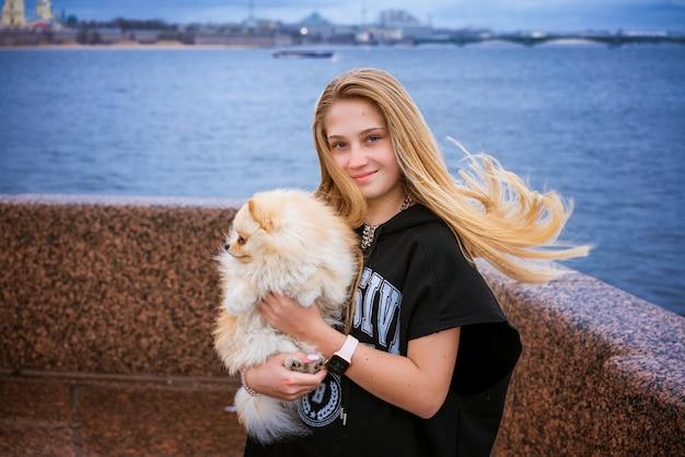 Adolescente de menina alegre e feliz detém e abraços spitz pomerânia em aterro na cidade em dia nublado.
