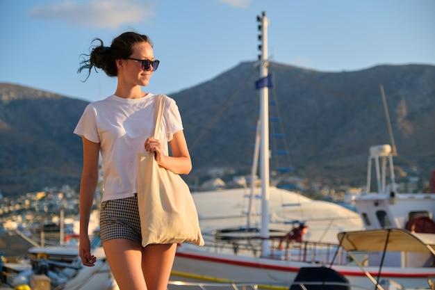 Adolescente de menina bonita elegante caminhando no cais, pôr do sol no mar, iates atracados na baía, fundo de paisagem de montanha. garota de óculos escuros, shorts e bolsa ecológica