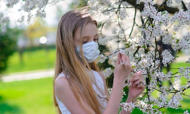 Adolescente de menina em máscara médica protetora na primavera entre jardim florescendo.