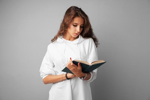 Adolescente de menina estudante com capuz branco, segurando um livro nas mãos dela, sobre um fundo cinza