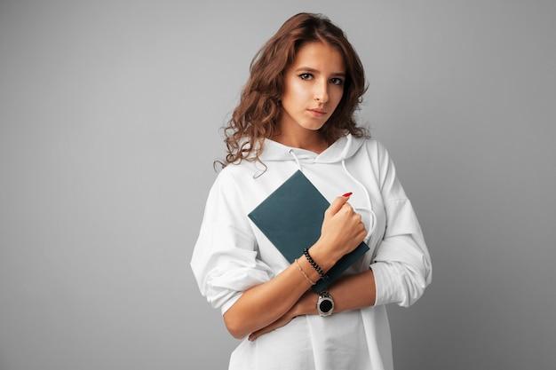Adolescente de menina estudante com capuz branco, segurando um livro nas mãos sobre um cinza
