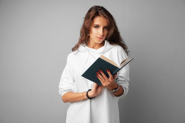 Adolescente de menina estudante com capuz branco, segurando um livro nas mãos