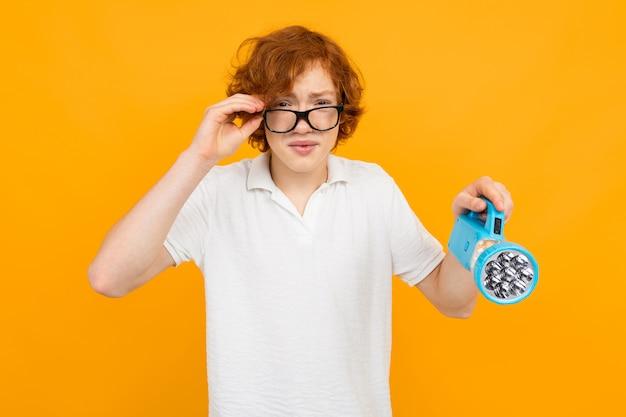 Adolescente de óculos e uma camiseta branca apertando os olhos enquanto segura uma lanterna na mão contra um amarelo