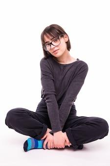 Adolescente de óculos sentada no chão isolada