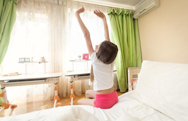 Adolescente de pijama se alongando ao lado da cama em uma manhã ensolarada