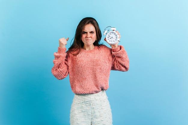 Adolescente de suéter rosa fica com raiva e fecha a mão em punho. menina de calça branca, posando com despertador.