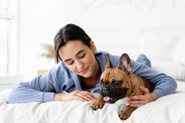 Adolescente de tiro médio e cachorro na cama