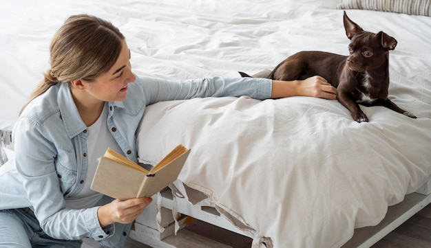 Adolescente de tiro médio lendo com cachorro