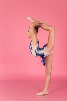 Adolescente de vestido azul, fazendo exercícios de ginástica em fundo rosa.