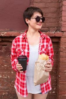 Adolescente de vista frontal segurando comida e café