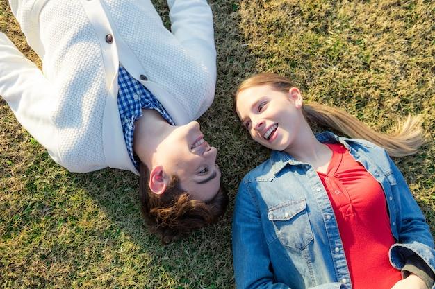 Adolescente deitado na grama com o namorado