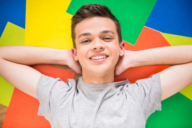 Adolescente deitado no chão colorido.