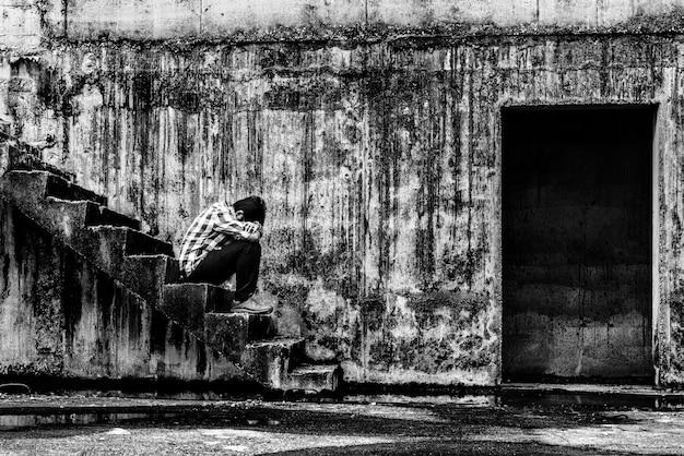 Adolescente deprimido sentado na escada no prédio assustador abandonado