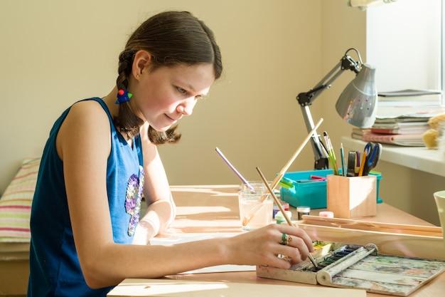 Adolescente desenha aquarela em uma mesa na sala