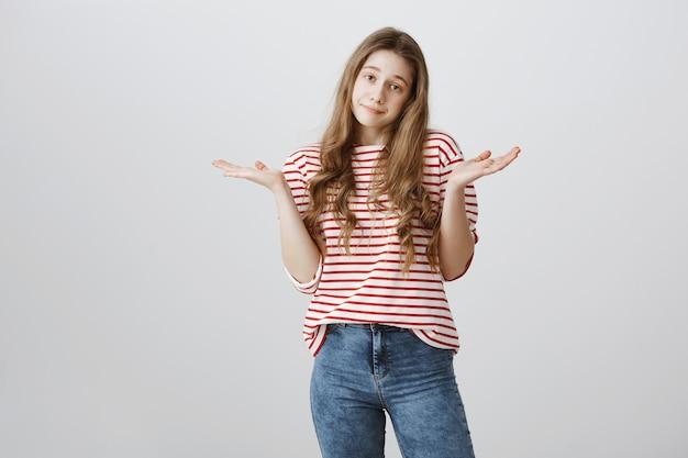 Adolescente despreocupada e despreocupada dando de ombros, não sei de nada